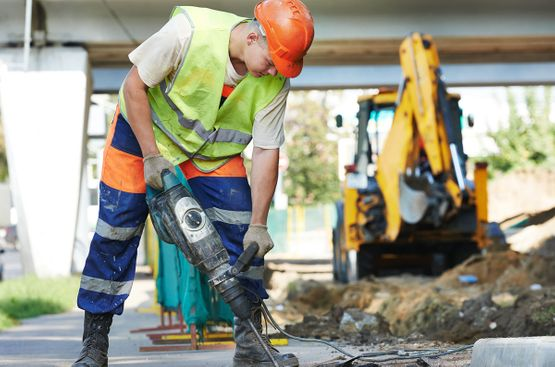 worker using a power tool to carry out ground repairs